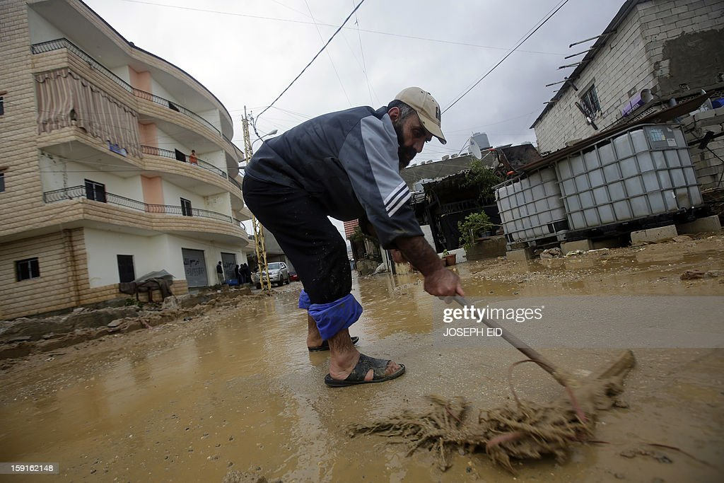 A man flushes water and mud from the entrance of his flooded house in Beirut's southern suburb of Hayy al-Sellum on January 9, 2013 as heavy rains and high speed winds hit Lebanon. A met office official at Beirut airport said the storm would continue and that lower temperatures would result in snowfall in the mountains as low as 300 metres.