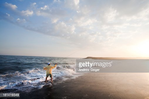 Man fly fishing in heavy surf. : Stock Photo