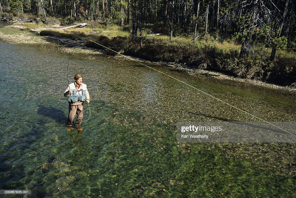 Man fly fishing in river elevated view stock photo getty for Fly fishing photography