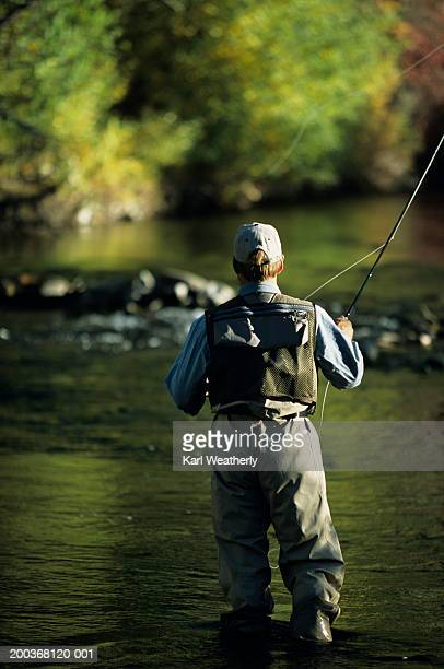 Man fly fishing in river, Rear view