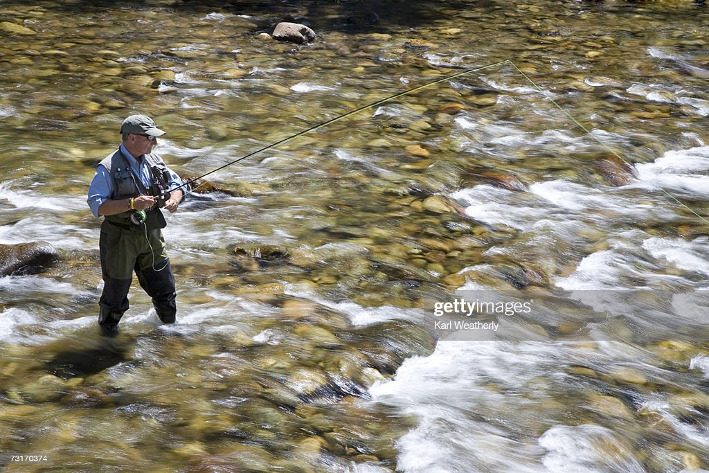 Man fly fishing in river side view stock photo getty images for Fly fishing photography
