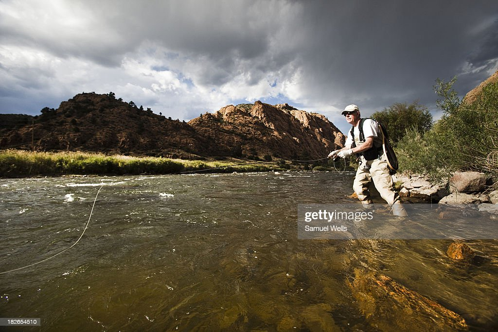 Man fly fishing in the arkansas river in colorado stock for Colorado fishing license fees