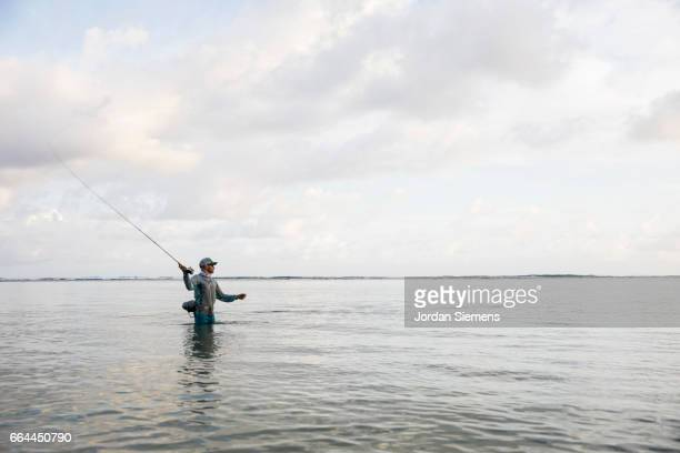 A man fly fishing in the ocean.