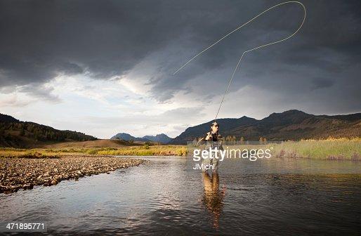 Man fly fishing knee deep in water