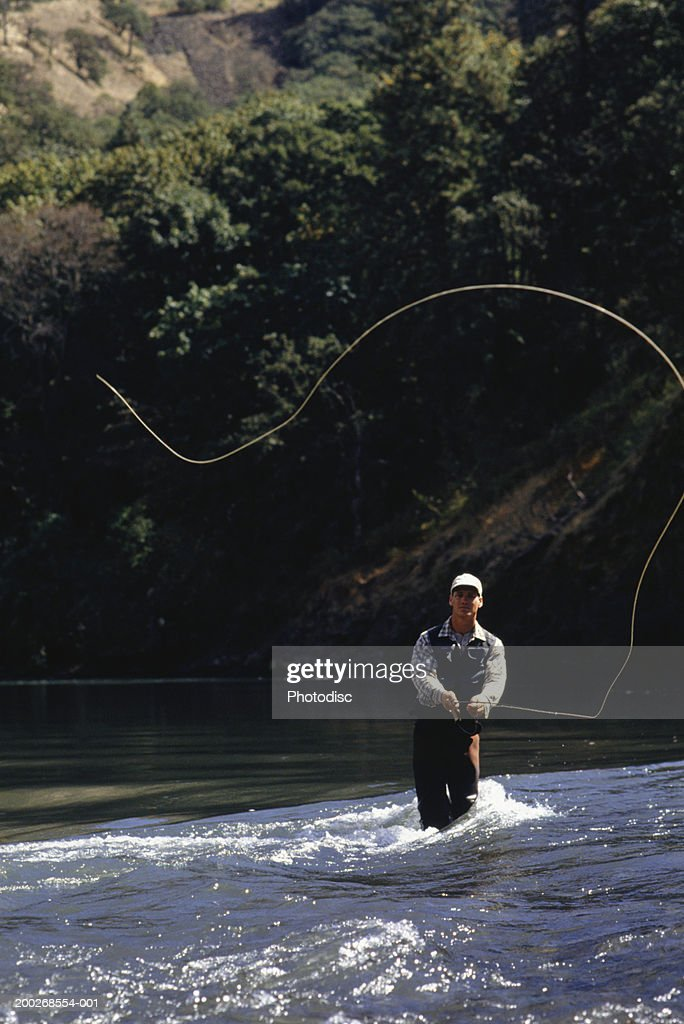 Man fly fishing on lake : Stock Photo