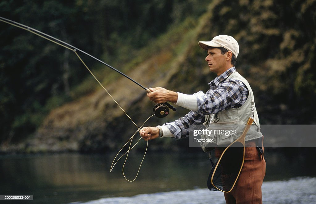 Man fly fishing, side view : Stock Photo