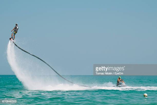 Man Flyboarding Over Sea Against Clear Sky