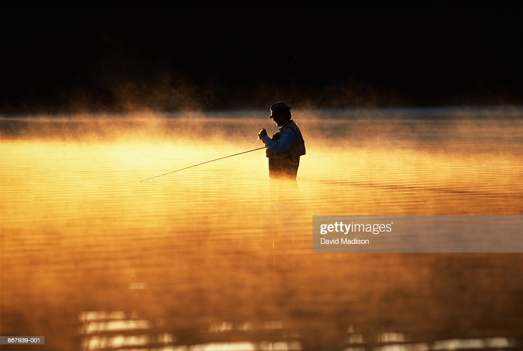 Man fly-fishing in river at dawn, with morning mist : Stock Photo