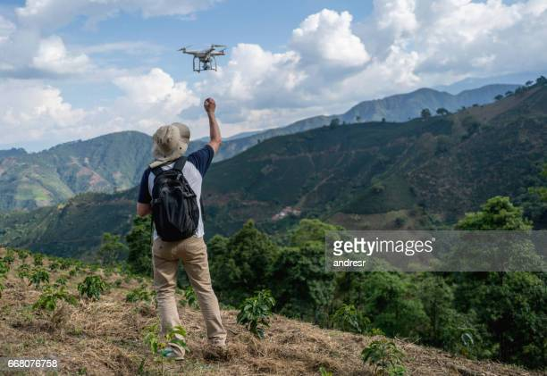 Man flying a drone in the countryside