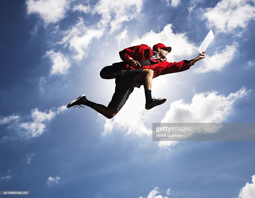 Man flying in air with letter in hand, against sky, low angle view : Stock Photo