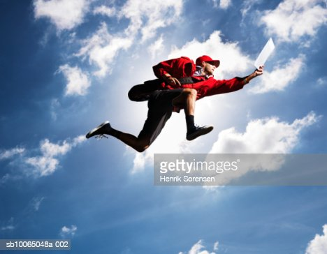 Man flying in air with letter in hand, against sky, low angle view : ストックフォト