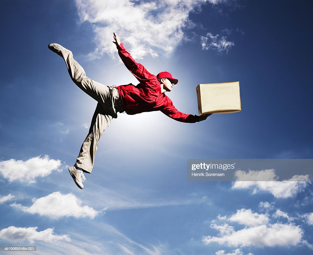 Man flying in sky with box in one hand, low angle view : Stock Photo