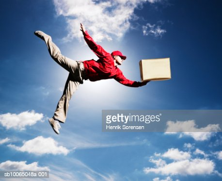 Man flying in sky with box in one hand, low angle view : Foto de stock