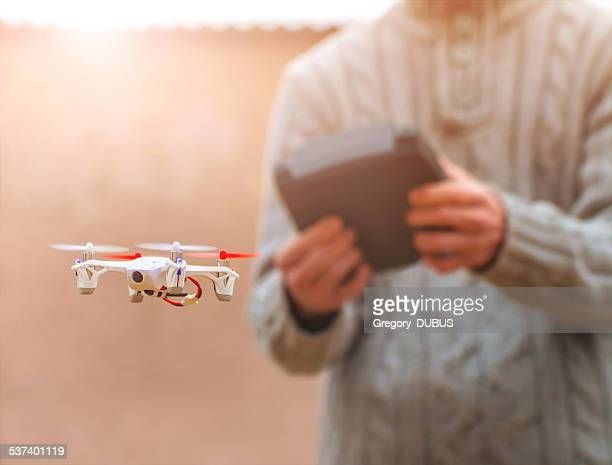 Man flying small drone at sunlight