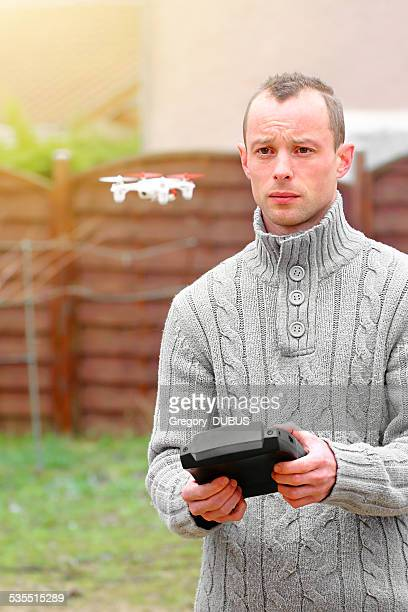 Man flying small drone using remote