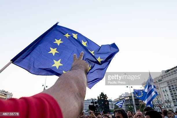 A man forms a 'victory sign' under a European Union flag While the Greek government is negotiating with their creditors with the Grexit scenario...