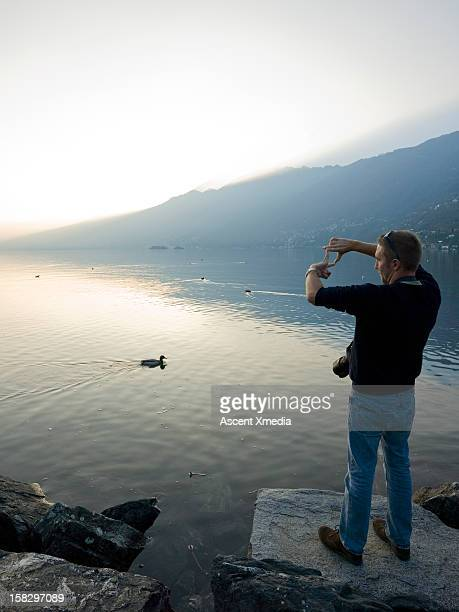 Man frames picture with hands, lake edge