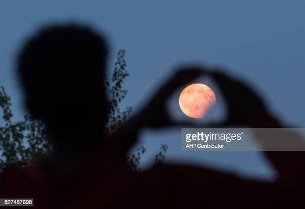A man frames with his hands the moon standing in a partial lunar eclipse on August 7 2017 in Frankfurt am Main western Germany / AFP PHOTO / dpa /...