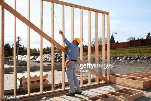 man framing a wall plumb and square stock photo