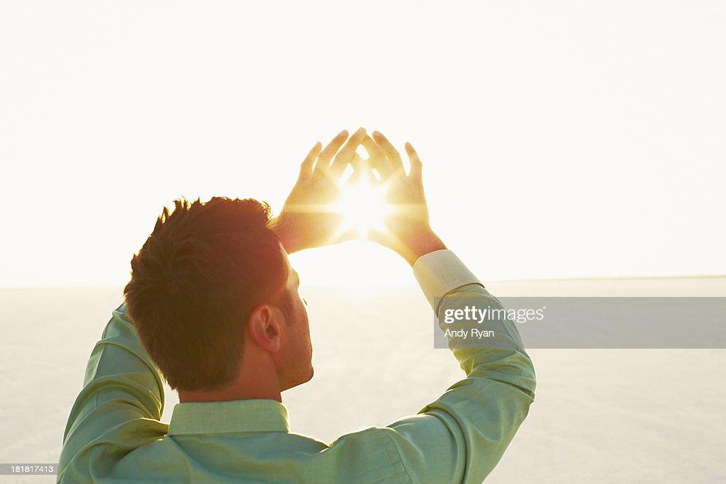 Man framing sun with hands. : Stock Photo