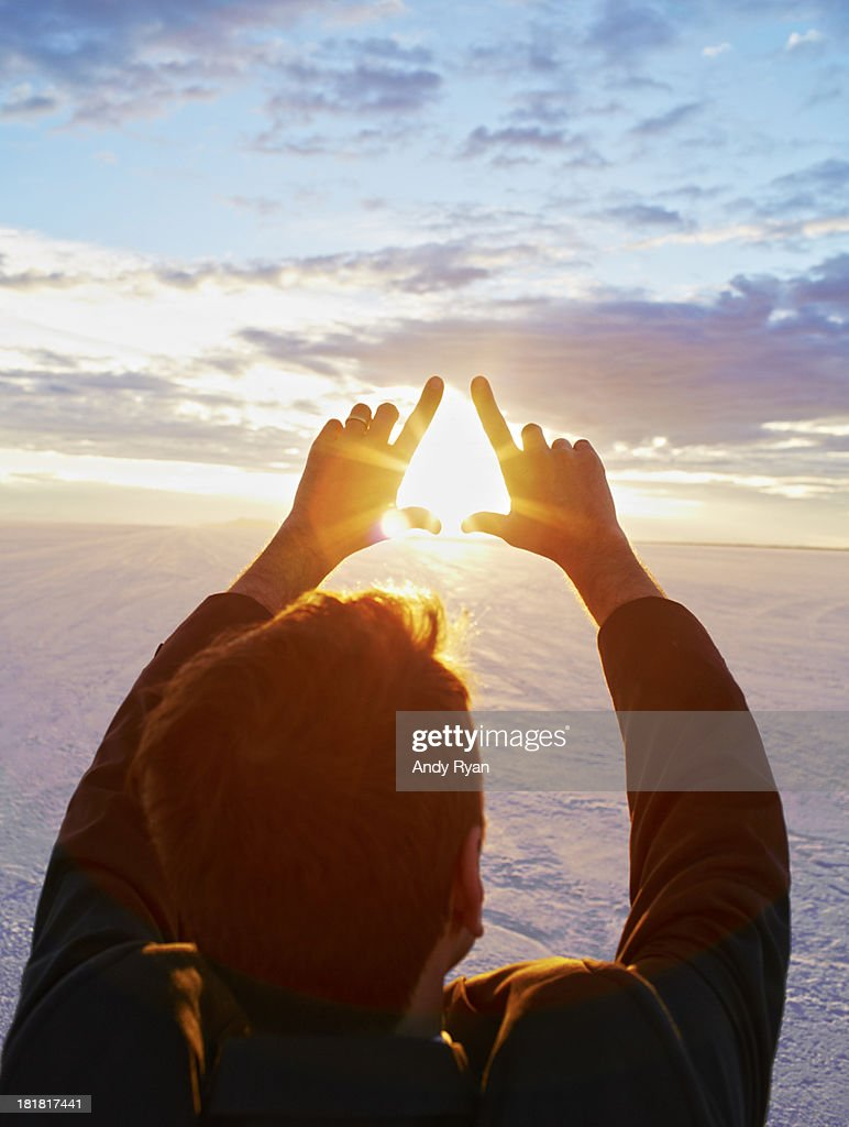 Man framing sunrise with hands, elevated view. : Stock Photo