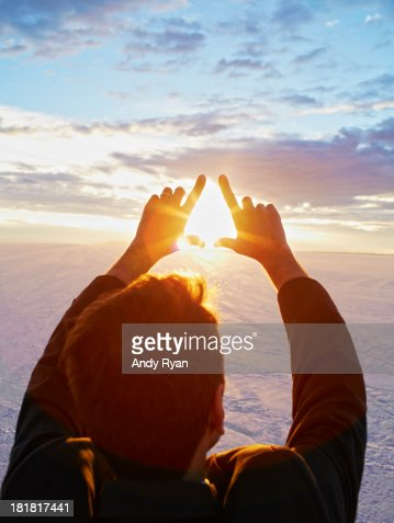 Man framing sunrise with hands, elevated view.