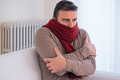 Man feeling very cold at home with warm clothes