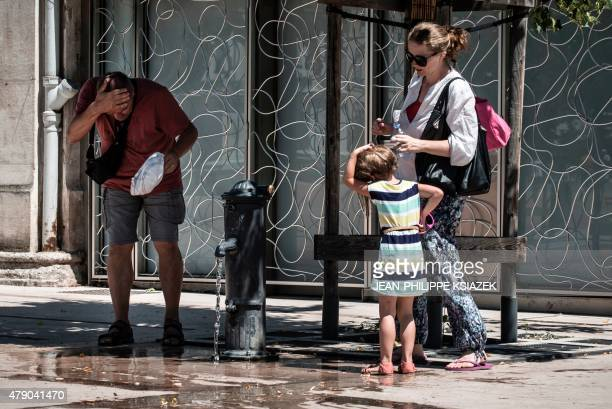 A man freshens up in a public fountain in Lyon on June 30 as a major heatwave spreads up through Europe with temperatures hitting nearly 40 degrees...