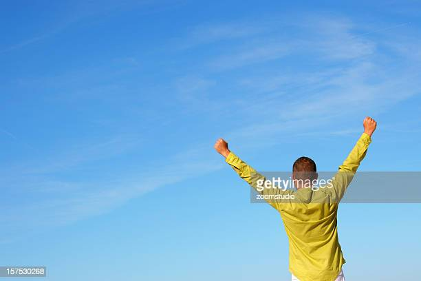 Man from behind in yellow shirt raising arms with blue sky