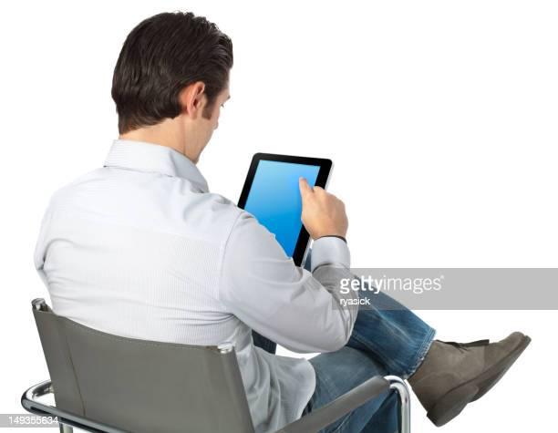 Homme assis dans une chaise derrière la navigation Smart tablette et décontractée