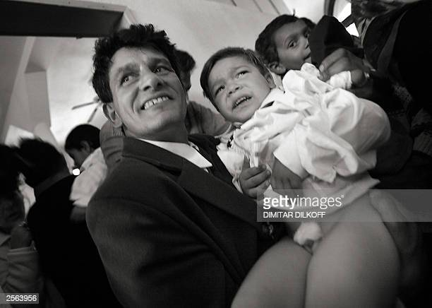 A man from from Bulgaria's ethnicTurkish minority proudly shows his son to his friends just after the young boy was circumcised during a mass...