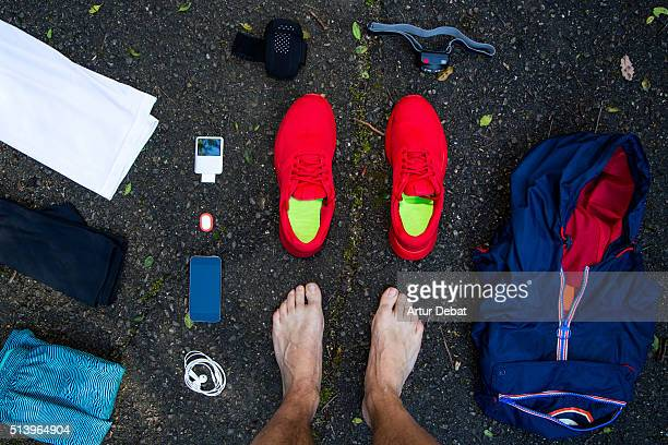 Man from personal point of view knolling all his running stuff for a race in a wet  dark asphalt in outdoors with nice composition and vivid colors.