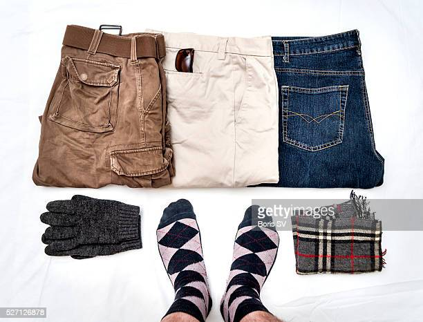 Man from personal point of view knolling his trousers