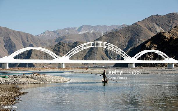 A man from Sichuan Province fishes in the Brahmaputra River by the crossing of the Caihong Railway Bridge along the QinghaiTibet railway in the Liuwu...