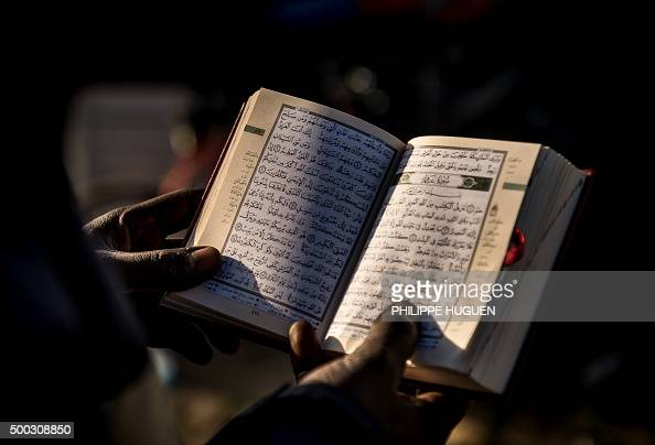 A man from Sudan reads the Koran at the migrant camp known as the 'Jungle' in Calais on December 7 2015 / AFP / PHILIPPE HUGUEN