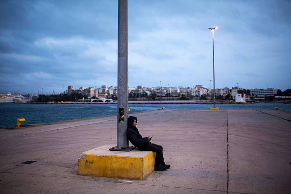 A man from Syria checks his mobile phone at Piraeus harbour, southwest of central Athens, on March 6, 2016. At least 25 migrants including children died on March 6 when their wooden boat capsized i...