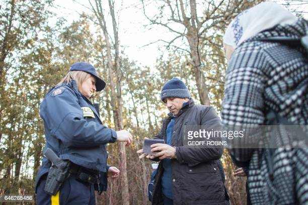 A man from Syria hands his family's passports to an RCMP officer after they illegally crossed the USCanada border near Hemmingford Quebec February 28...