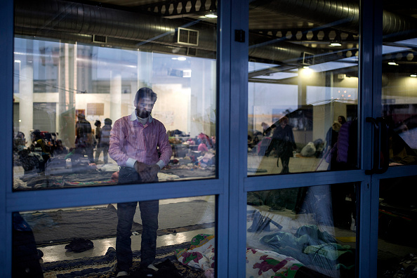A man from Syria prays in a makeshift migrant and refugee camp inside a passenger terminal at the Piraeus harbour, in Athens, on March 6, 2016. At least 25 migrants including children died on March...