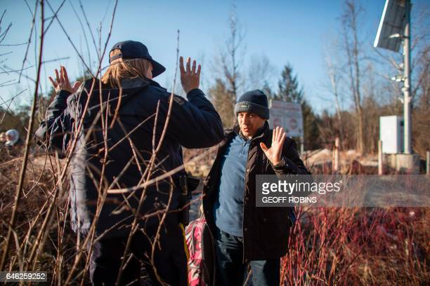 TOPSHOT A man from Syria raises his hands after bumping into an RCMP officer as he illegally crosses USCanada border near Hemmingford Quebec February...