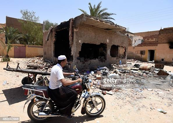 A man from the Berber community rides a motorcycle past a damaged house on July 9 following clashes between Berbers and Arabs in the Algerian town of...