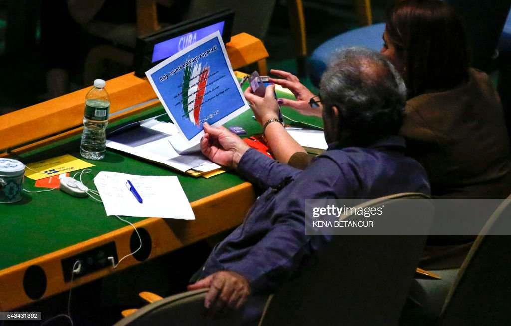 A man from the delegation of Cuba reads a poster left by the Italians members to promote their country before the fourth round of voting in the Election of five non-permanent members of the Security Council at the United Nations in New York on June 28 2016. / AFP / KENA