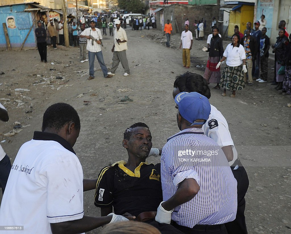 A man from the Somali community is carried by medics after he was injured when police dispersed large crowds at the scene of a suspected bomb attack in Nairobi's Eastleigh suburb, on November 18, 2012. Seven people were killed and many more wounded when an apparent explosive device was hurled at a packed minibus in a predominantly Somali area of the Kenyan capital Nairobi today, police and the Red Cross said. Nairobi police chief Moses Nyakwama said the blast occurred on a so-called 'matatu', or local minibus, in the district of Eastleigh, where mainly Somalis or Kenyans of Somali origin live and which has been the target of other attacks in recent weeks. AFP PHOTO/Tony KARUMBA