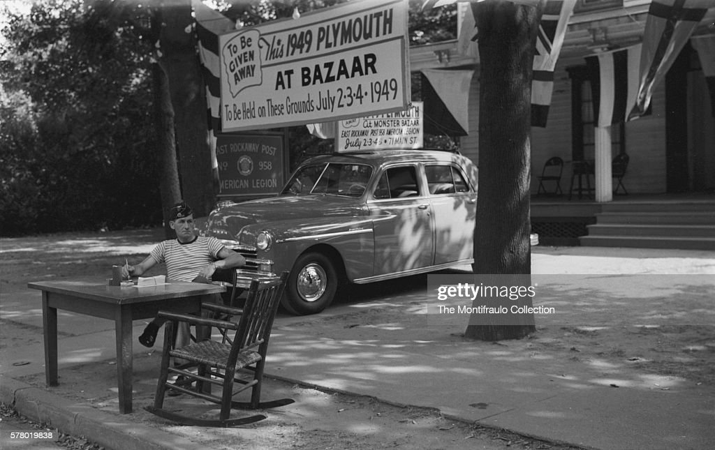 A man from the the American Legion sits beside a road selling raffle tickets with the prize a 1949 Plymouth car on view behind him Just above the car...