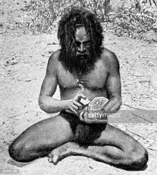 A man from the Warramunga tribe making a stone axe head Australia 1922 The man is chipping a block of diorite by means of a small lump of hard...