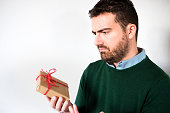 Funny face of a man disappointed by the small gift box , empty copy space for text