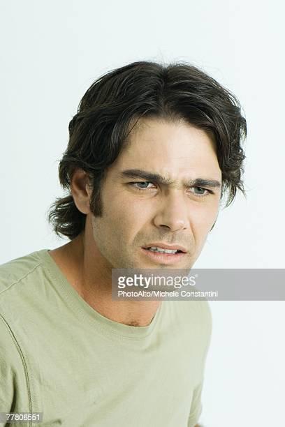Man furrowing brow, looking away, portrait