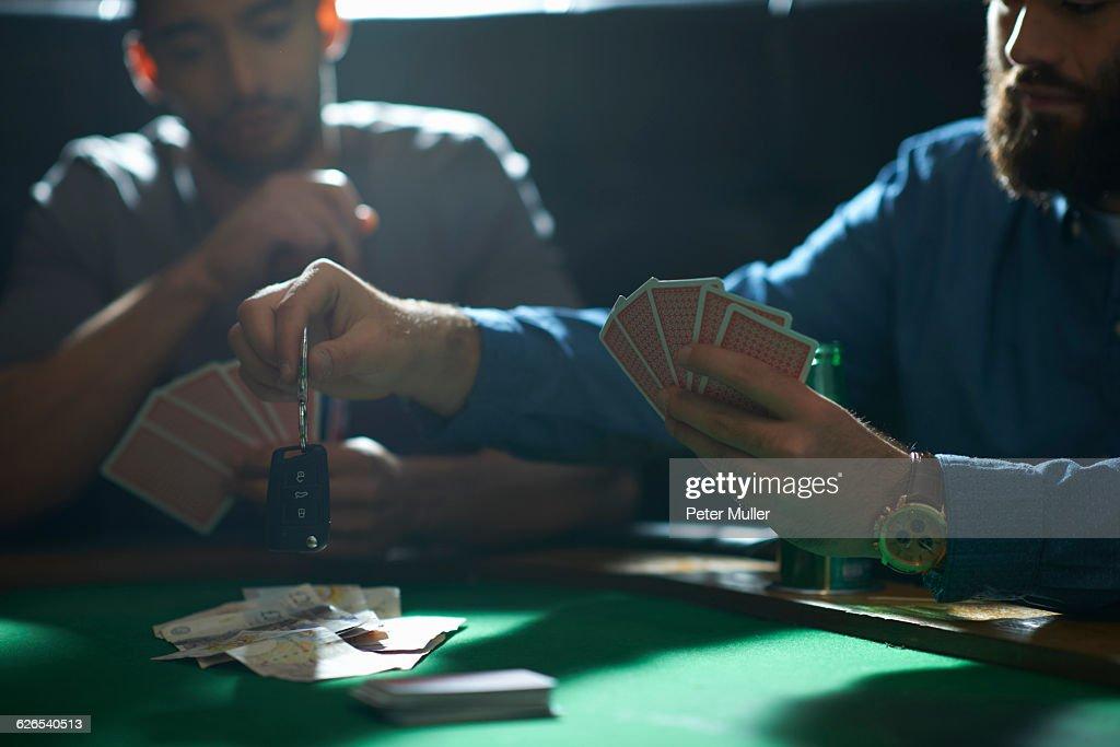 Man gambling car key playing card game at pub card table