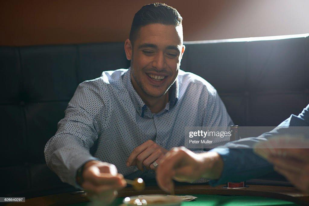 Man gambling key playing card game at pub card table