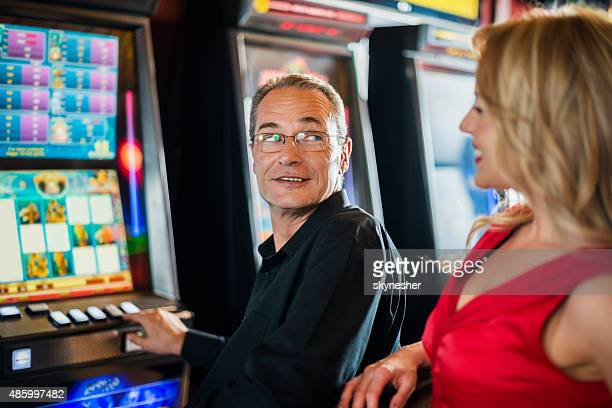 Uomo, gioco d'azzardo a slot machine e parlando di una donna.