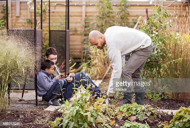 Man gardening at yard with children in background